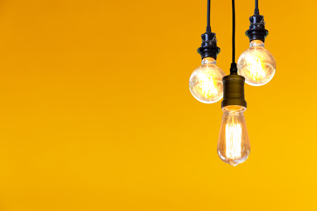 vintage-light-bulb-hanging-yellow-background_48277-134